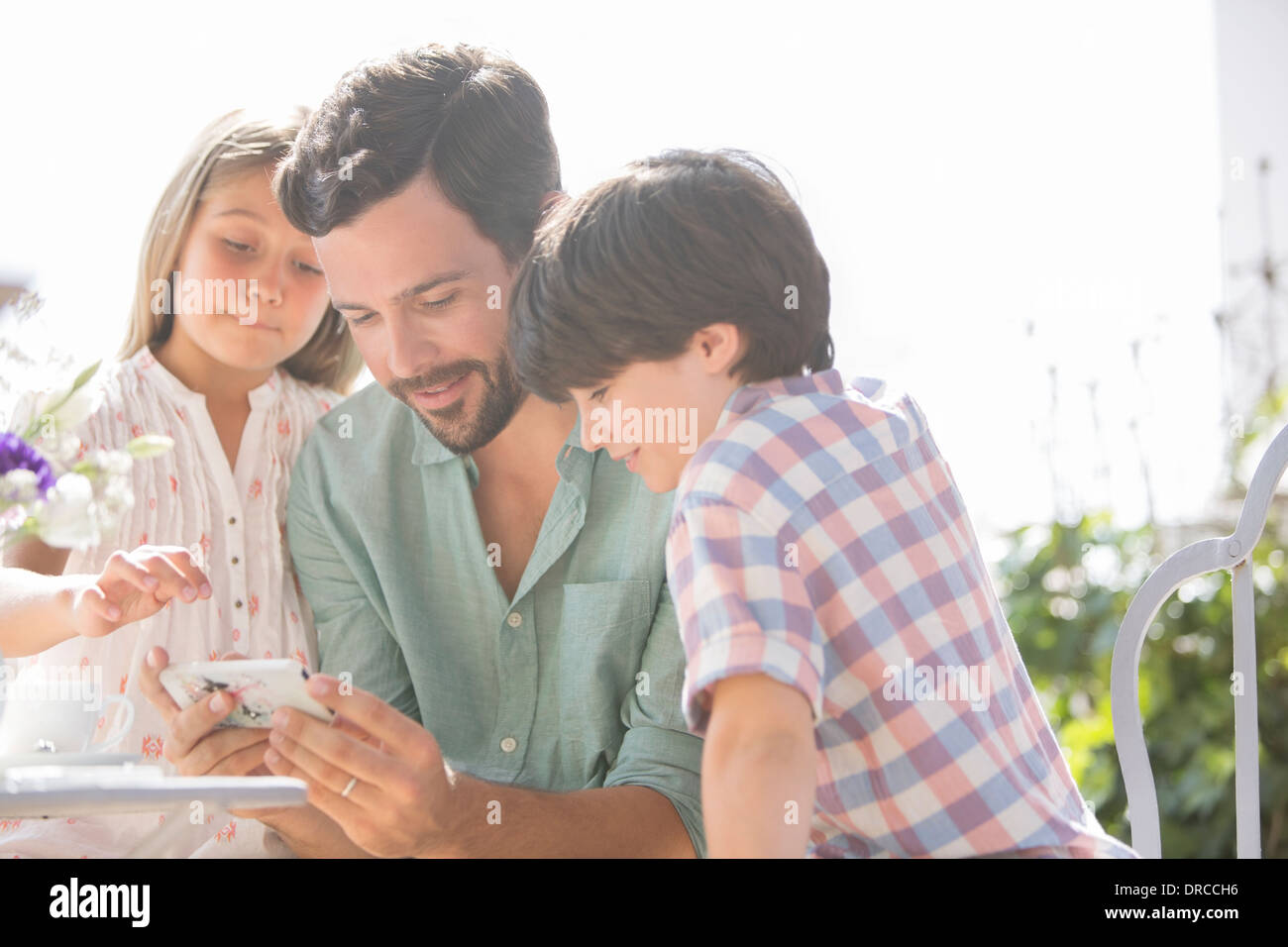 Father and children using cell phone outdoors - Stock Image