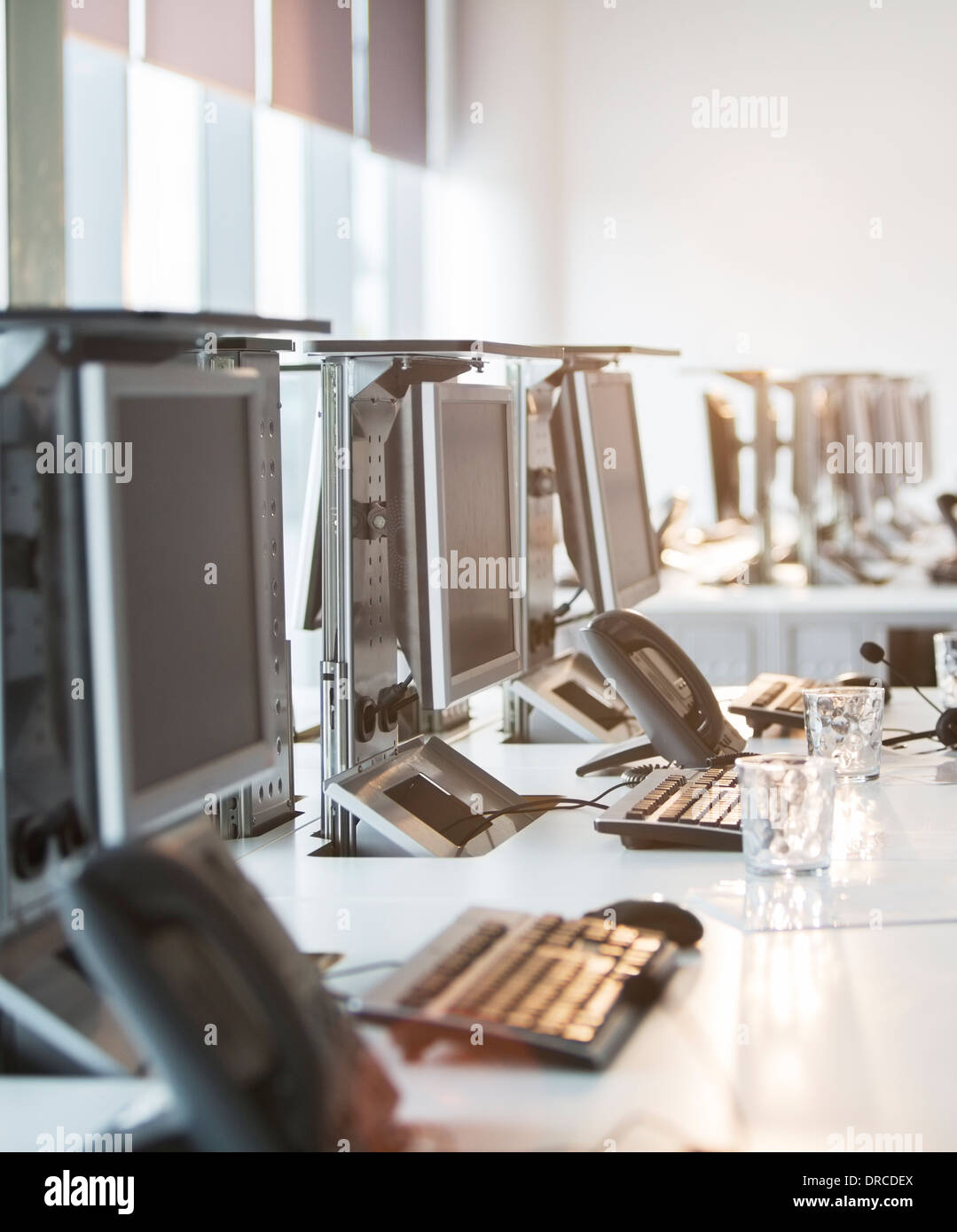 Computers and telephones at desk in office - Stock Image