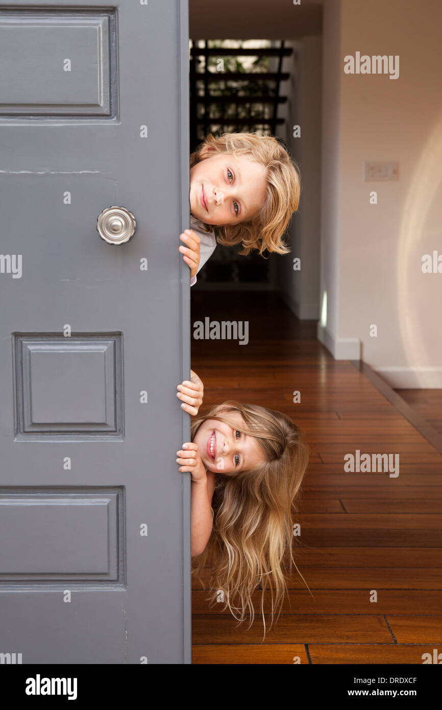 Siblings peeking out door - Stock Image