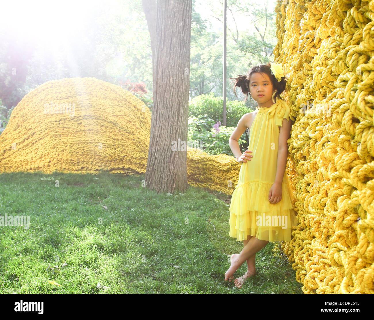 Young asian girl in yellow dress near yellow wall - Stock Image