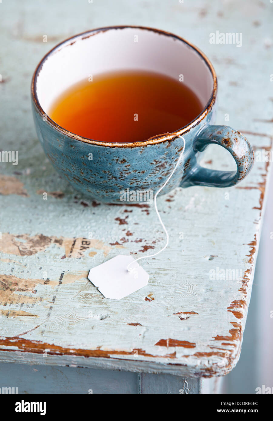 Cup of tea with teabag on blue textural background - Stock Image
