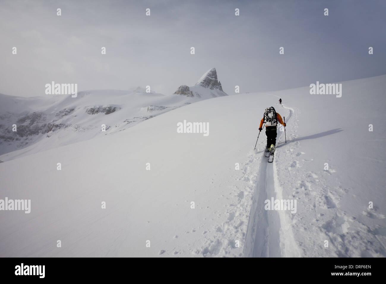 Alberta Canada. Two skiers ascending ridge in mist and cloud Wapta Traverse - Stock Image