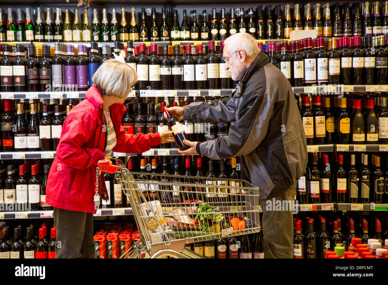 Older couple buys in a supermarket. Wine and liquor department. Stock Photo