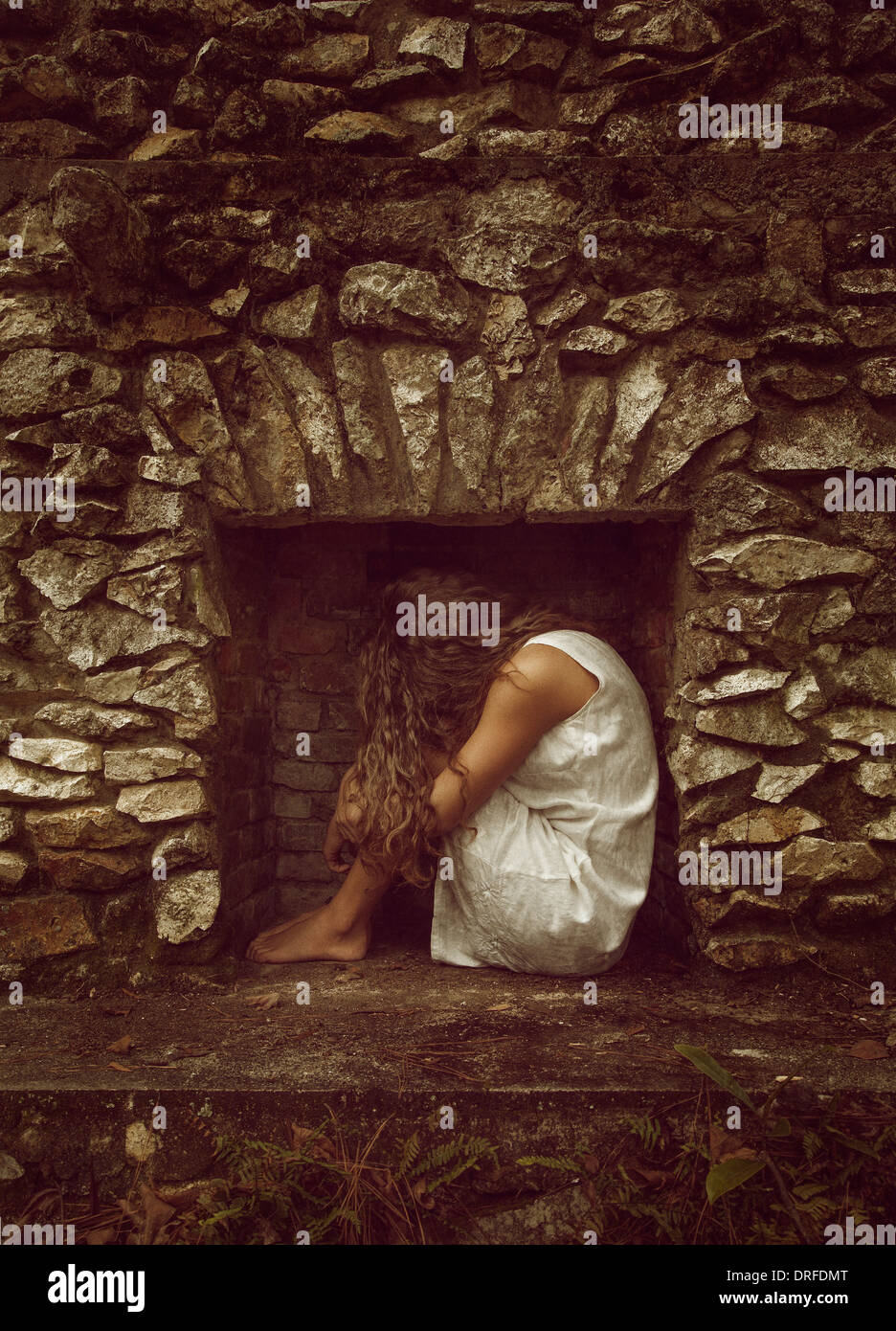 Woman curled up in fireplace in white dress - Stock Image