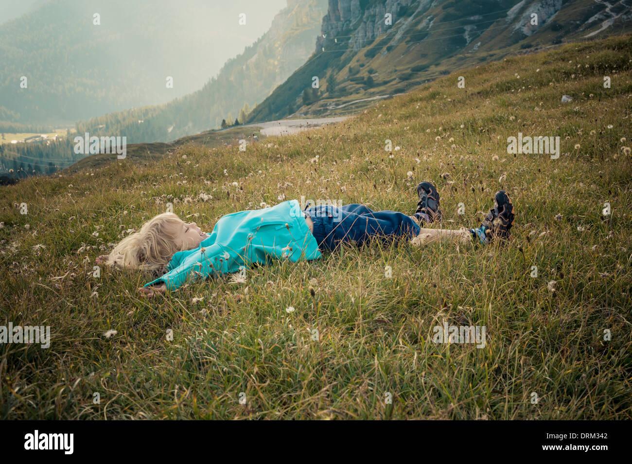 Italy, Province of Belluno, Veneto, Auronzo di Cadore, little boy lying on alpine meadow near Tre Cime di LavaredoStock Photo