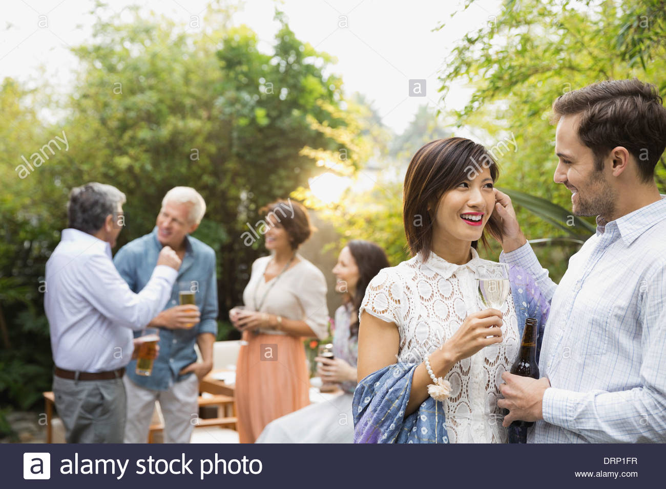Couple with drinks at outdoor party - Stock Image