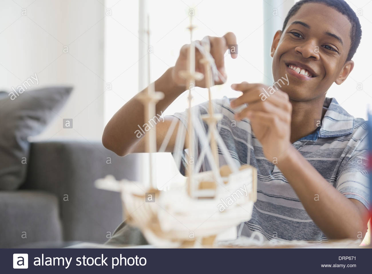 Teen building ship model at home - Stock Image