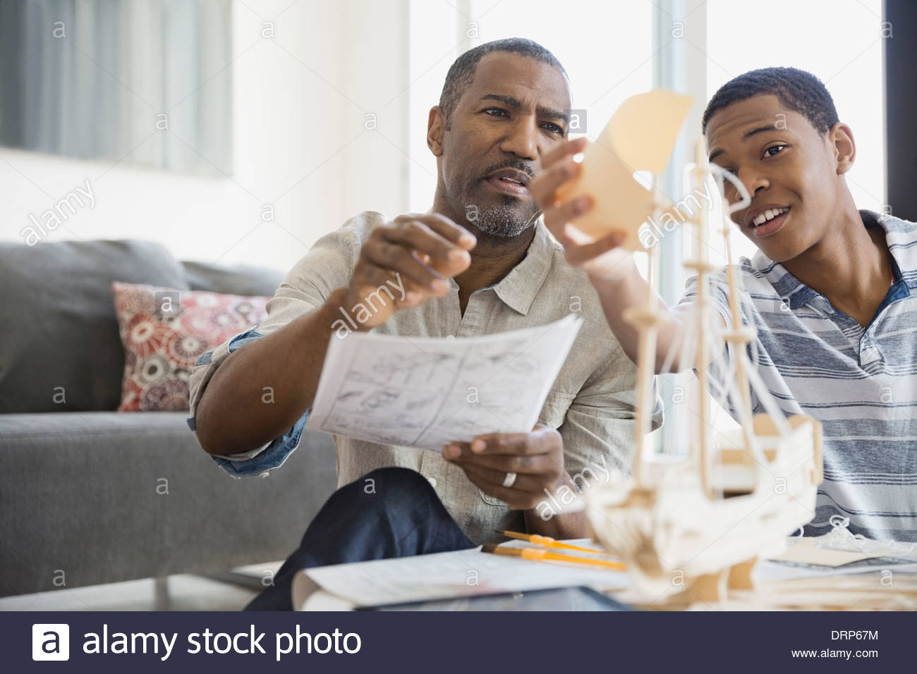 Father and son building ship model at home - Stock Image