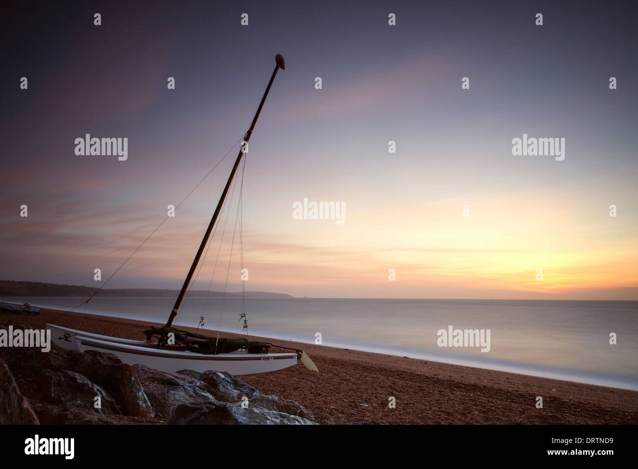 A small sailing boat on the beach at Beesands in South Devon in summer at sunrise. - Stock Image