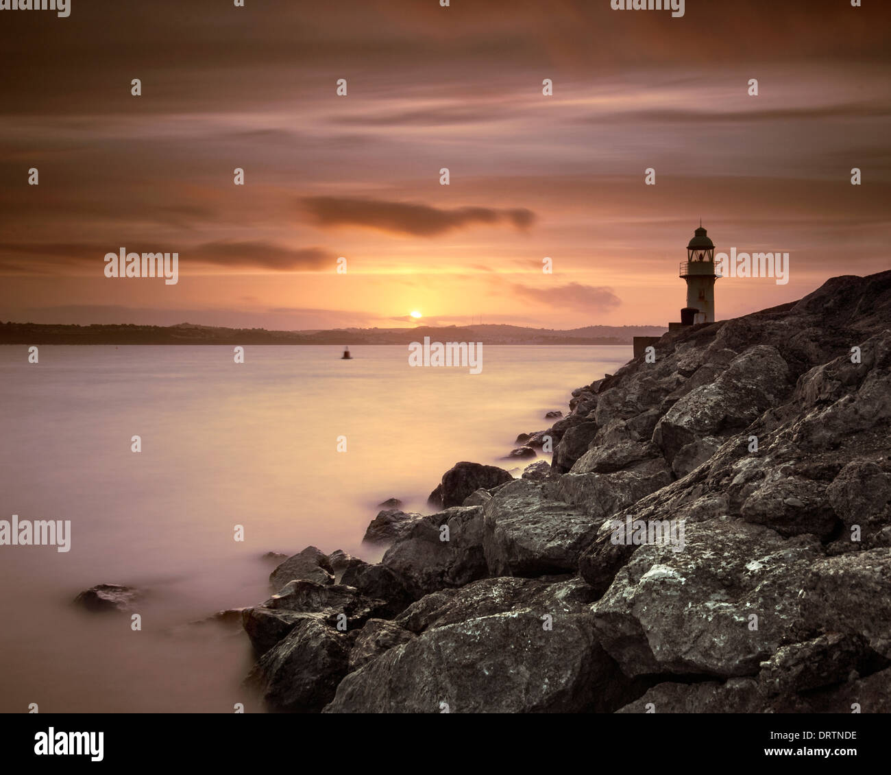 Brixham lighthouse at the end of the breakwater at sunset. - Stock Image