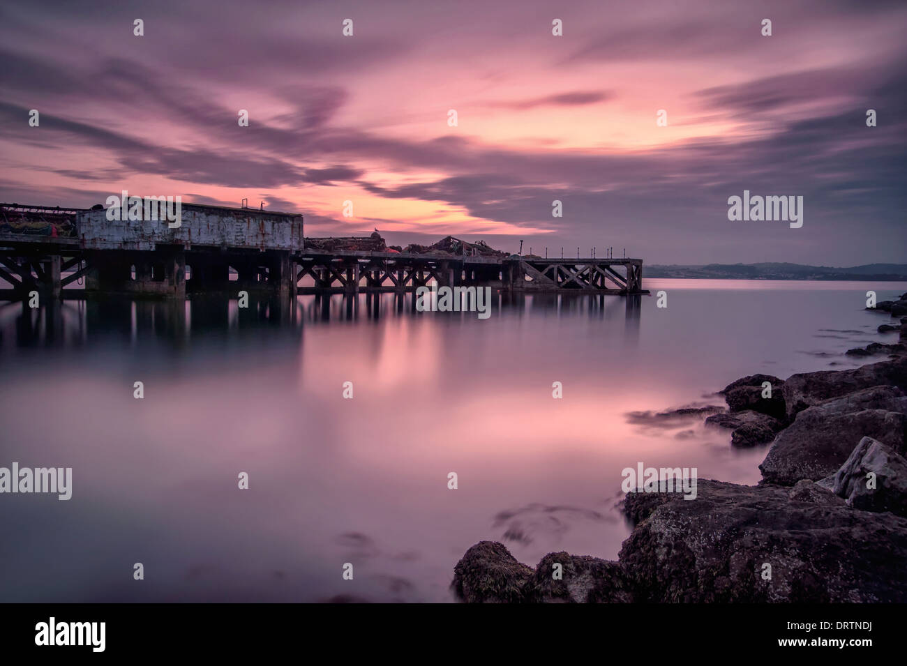 Brixham jetty  / pier in Torbay Devon early evening which joins the breakwater. - Stock Image
