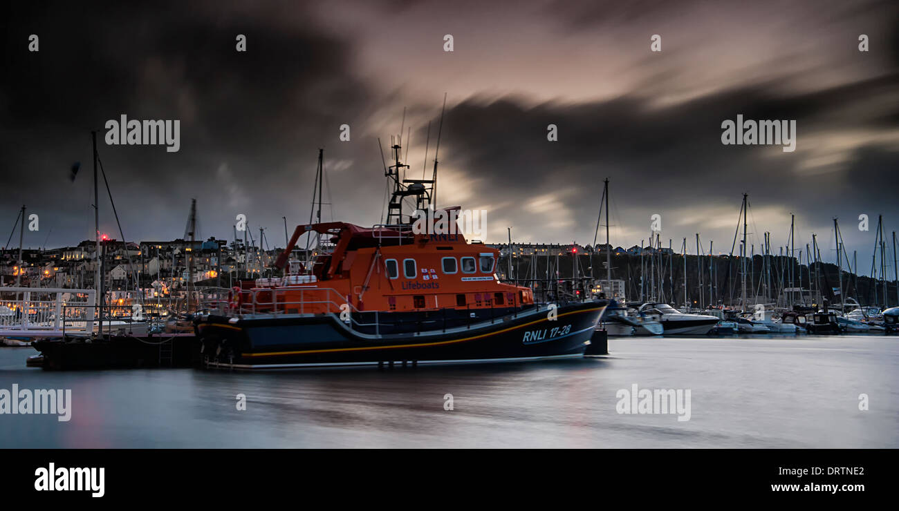 Torbay RNLI 17-28 Lifeboat based in Brixham moored up during a storm. The harbour and marina can be seen in the - Stock Image