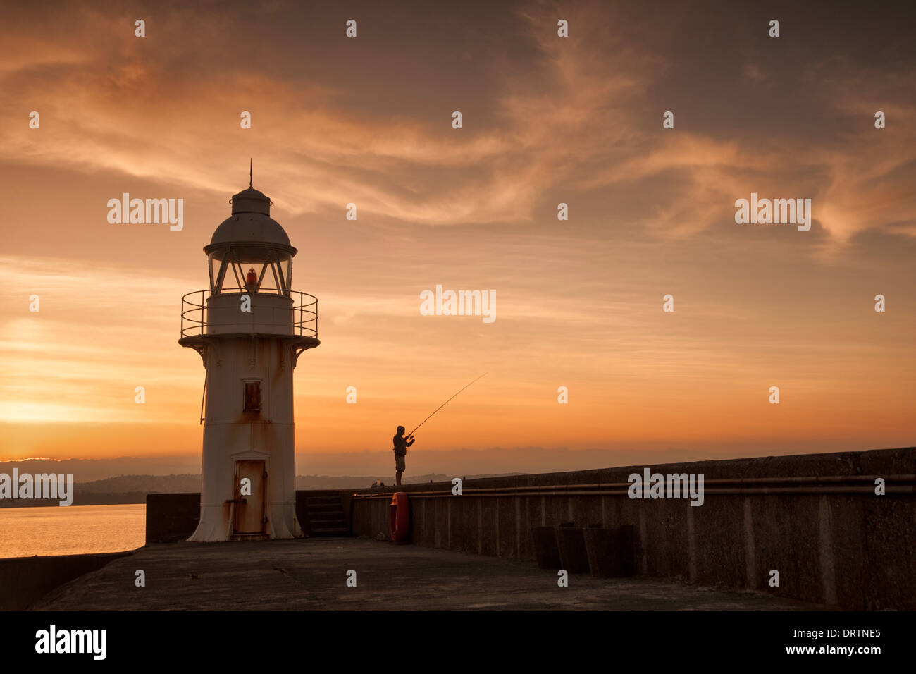 Lighthouse and breakwater in the coastal fishing port of Brixham, South Devon with a pleasure fisherman taken at - Stock Image