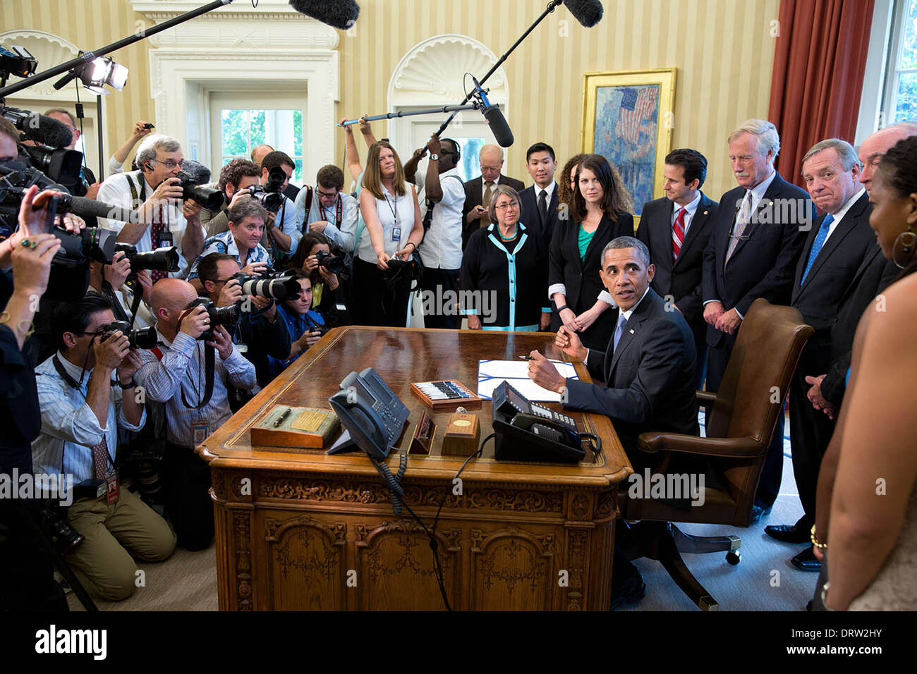US President Barack Obama looks back towards a group of students before signing H.R. 1911, the Bipartisan Student - Stock Image