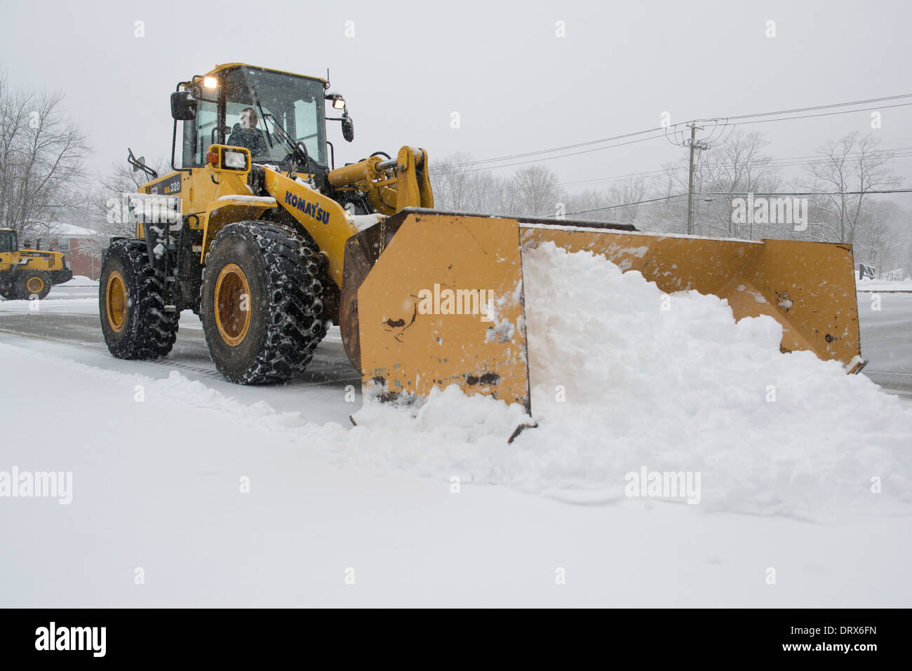 Plowing snow with Komatsu tractor at SCSU. - Stock Image