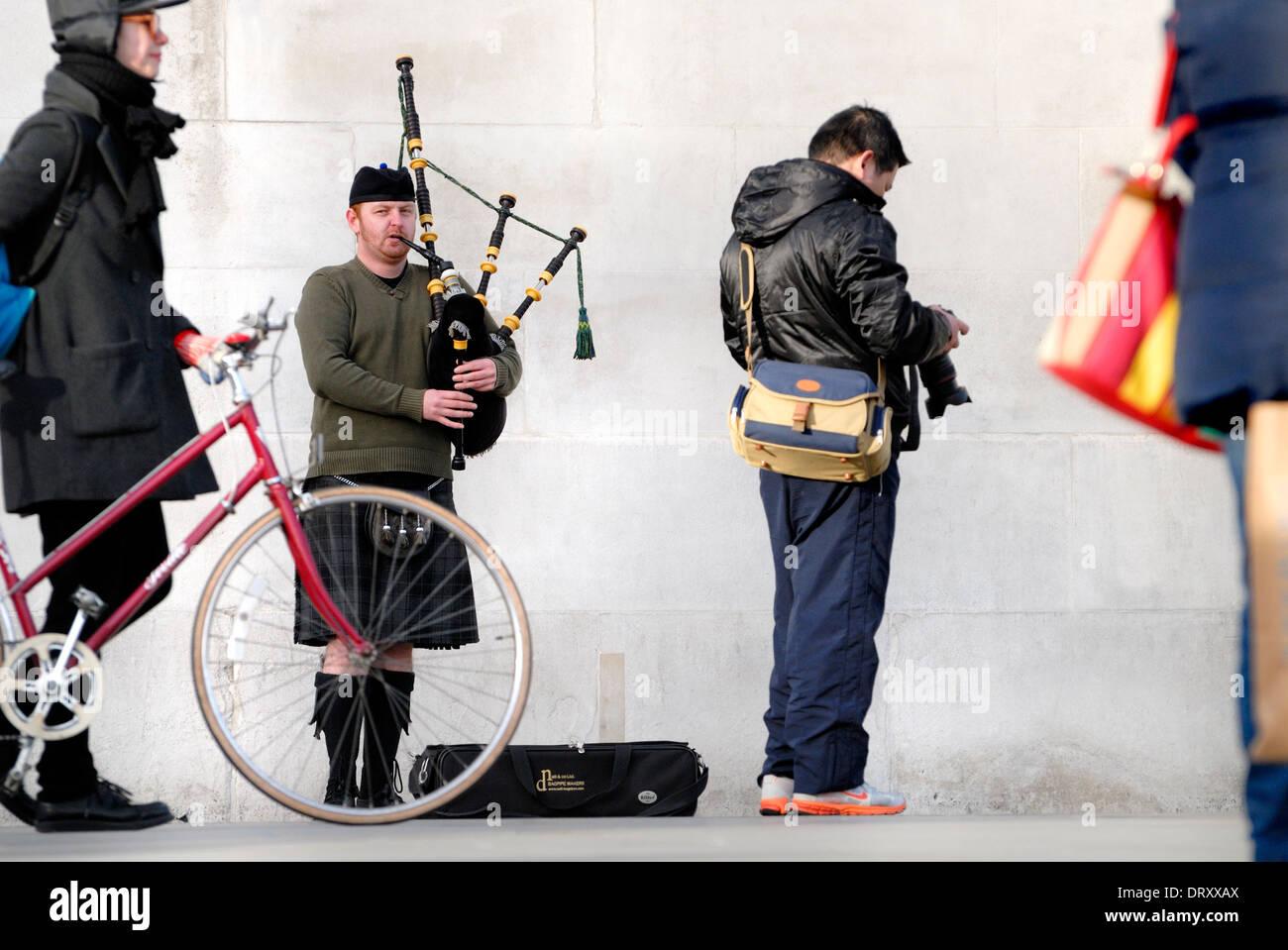 london-england-uk-busking-bagpiper-in-trafalgar-square-DRXXAX.jpg