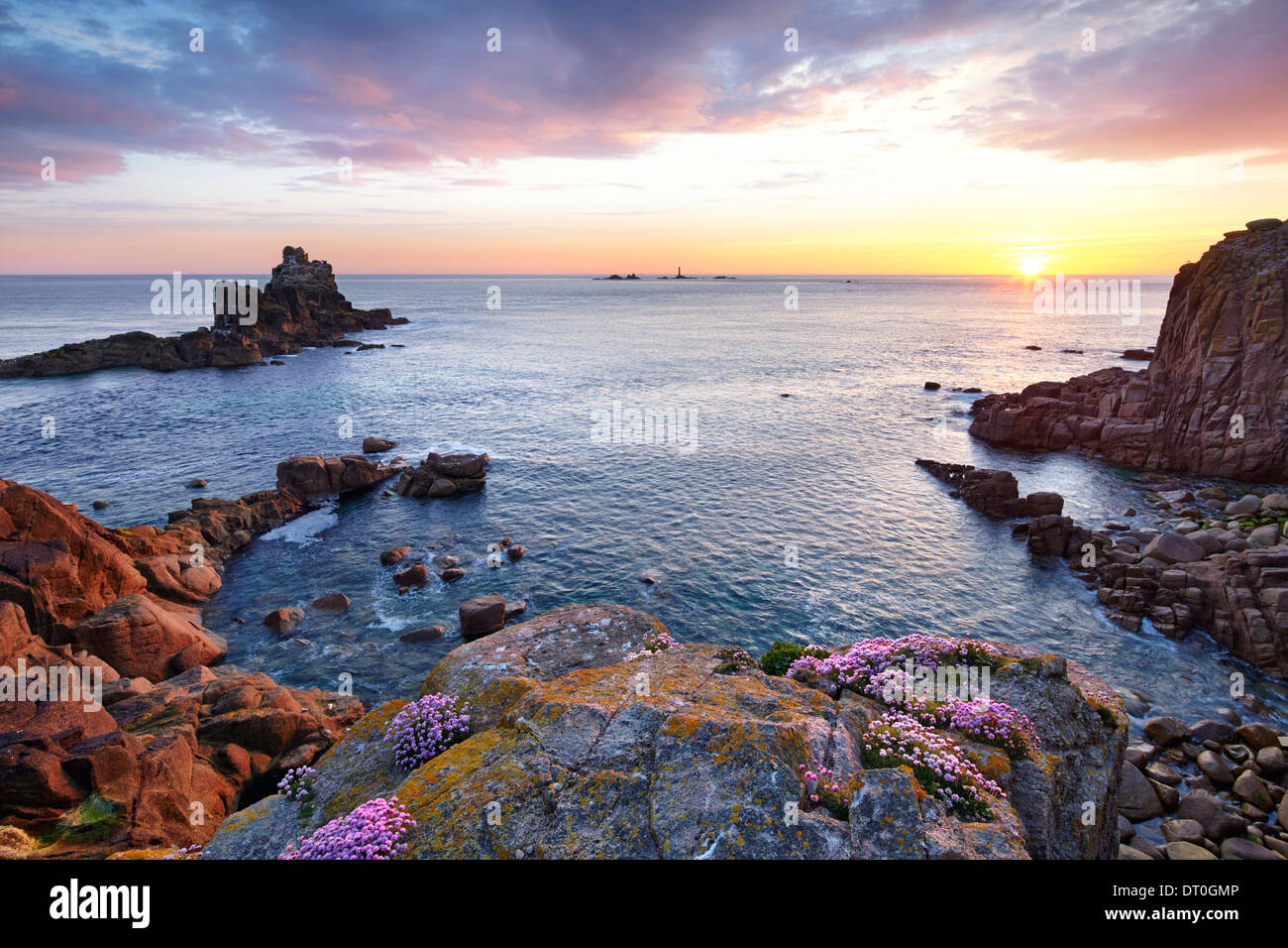The sun setting at Land's End with thrift clinging to the rocks. - Stock Image