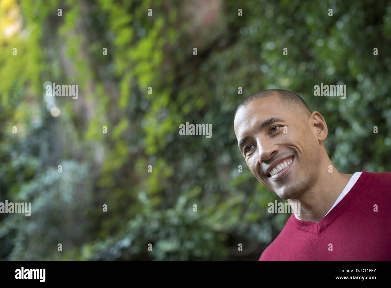Scenes from urban life in New York City A man smiling in a relaxed mood in a leafy space - Stock Image