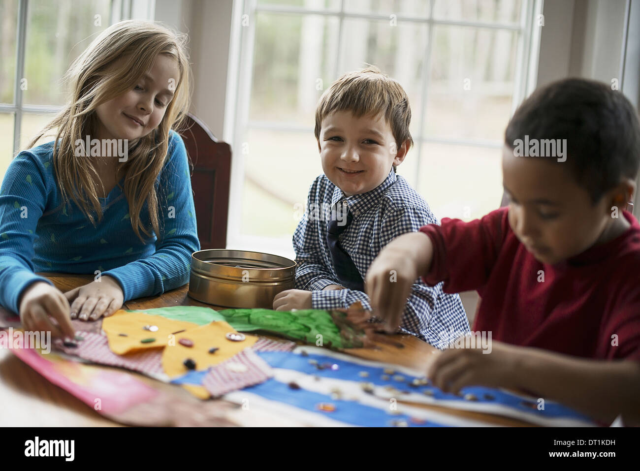 Children in a family home Three children creating pictures with glue and stickers Craftwork - Stock Image