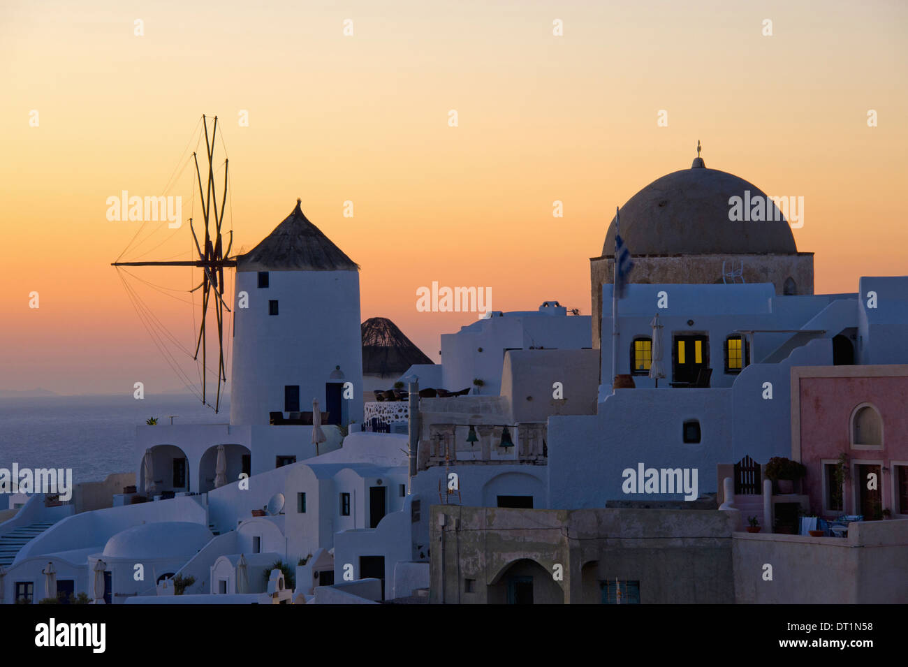 The historic white washed houses windmills and domed church of Oia town on Santorini island - Stock Image