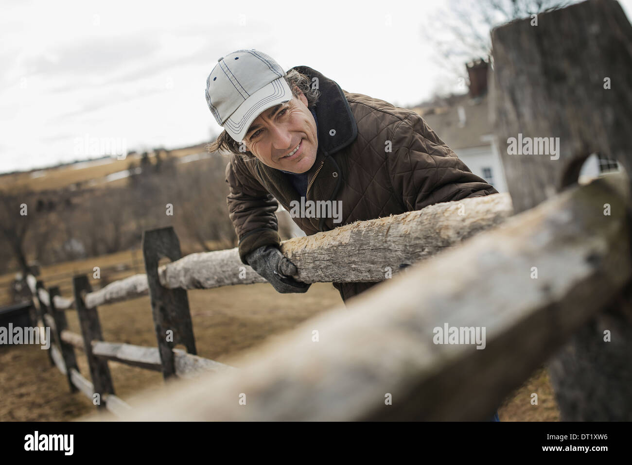 A man leaning against a post and rail fence on a farm in winter - Stock Image