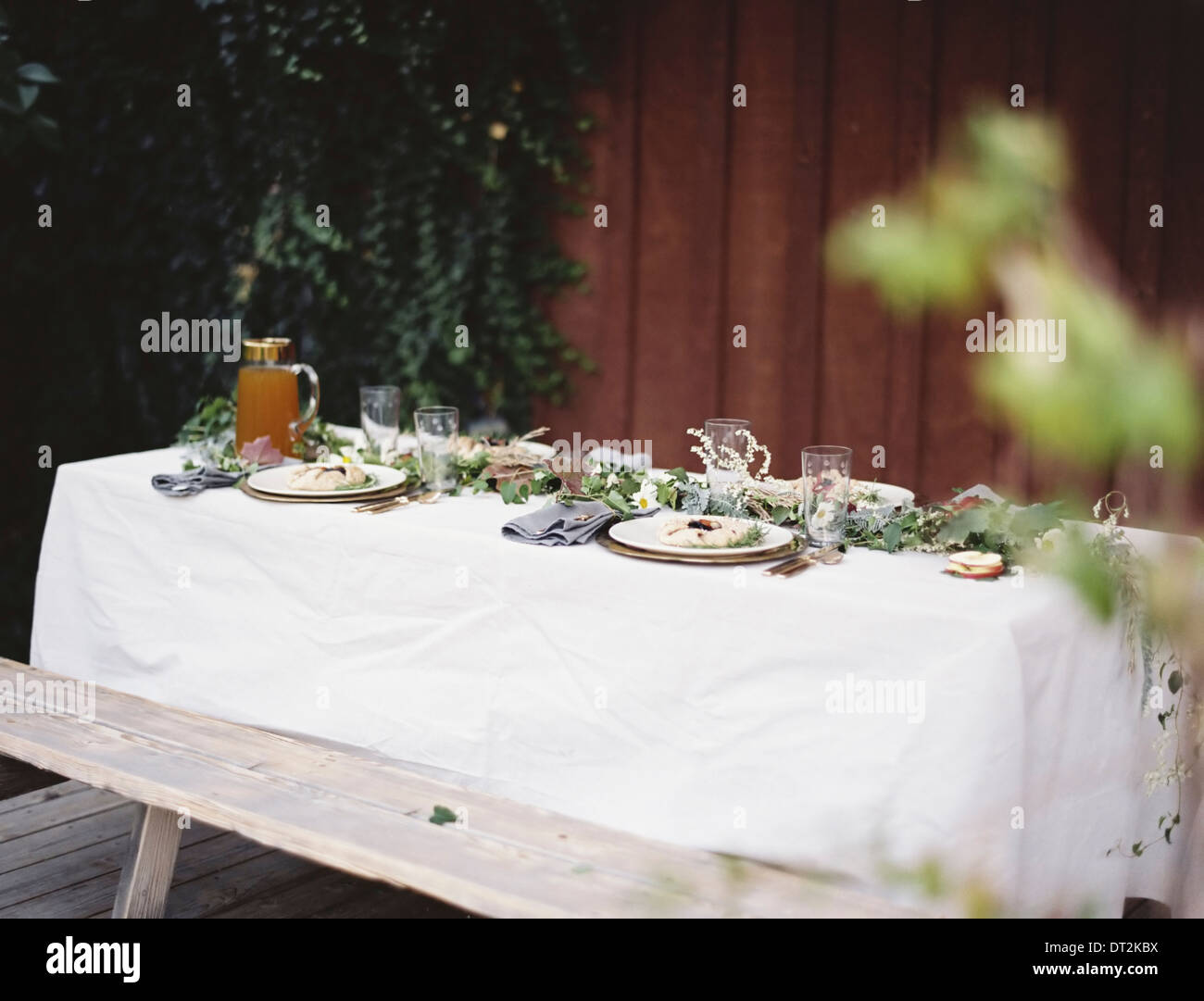 A Table Laid For A Special Meal Place Settings With Plates And Cutlery  Glasses A White Table Cloth And Bench Seat Plates Of Food