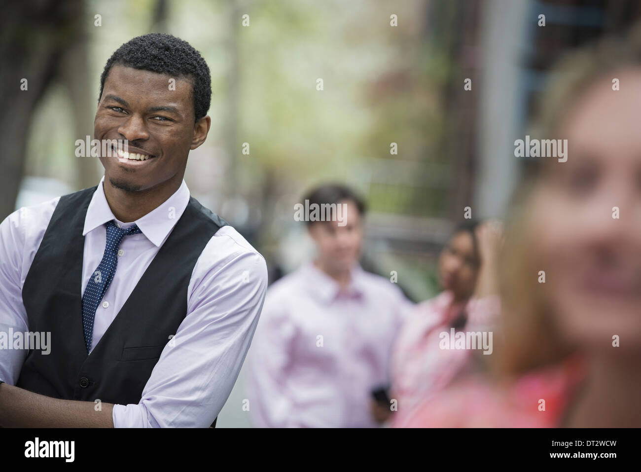 View over cityYoung people outdoors in city park A man with arms folded smiling and three other people grouped around - Stock Image