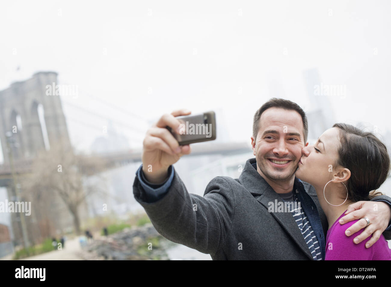 Brooklyn Bridge crossing over the East River A couple taking a picture with a phone a selfy of themselves - Stock Image