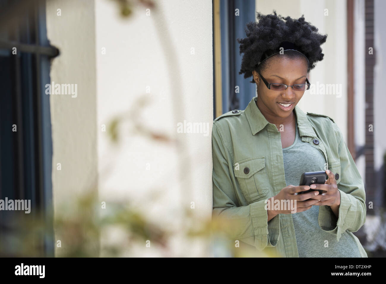 A woman leaning against a doorframe checking her phone - Stock Image