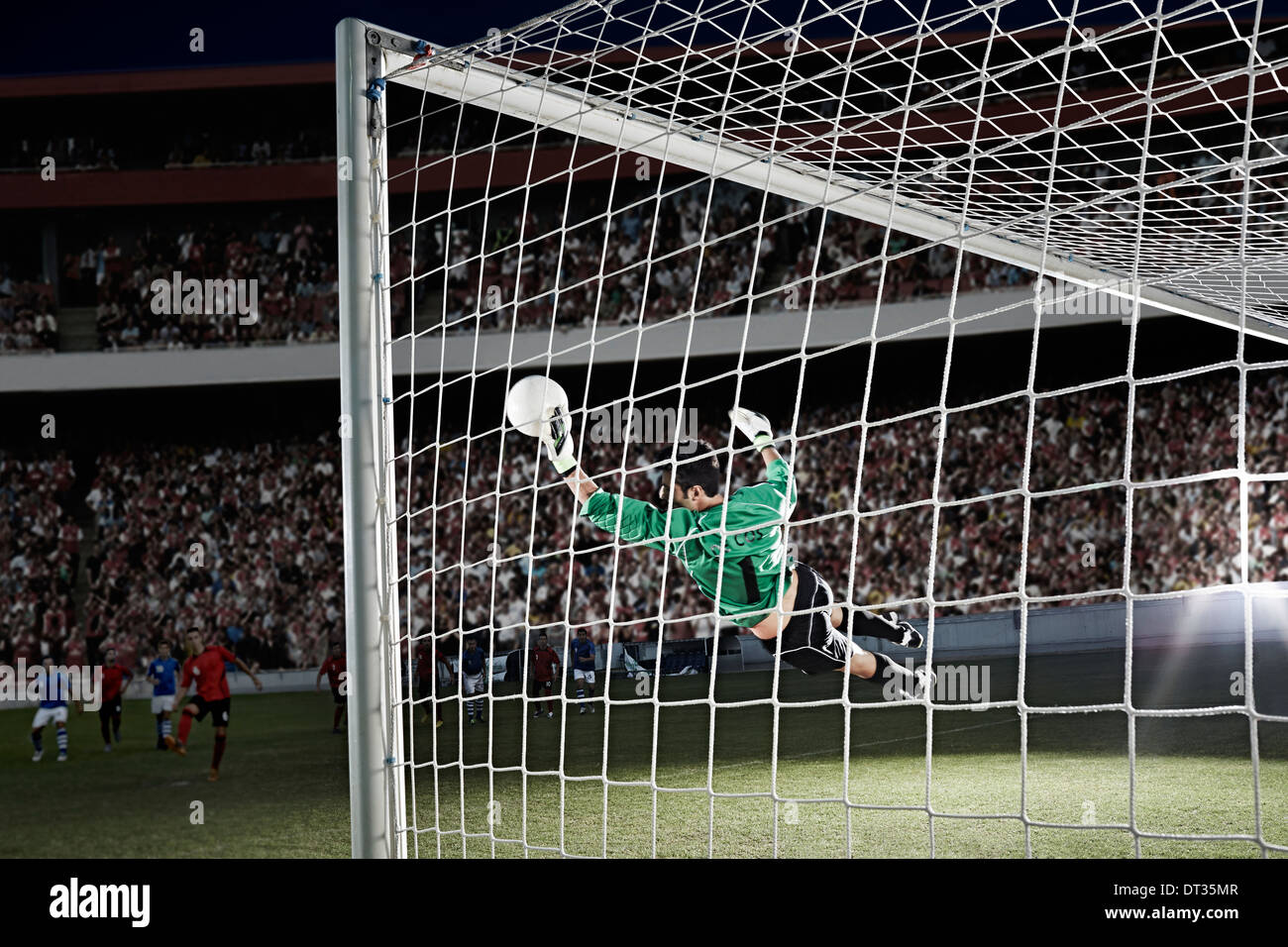 Goalie defending soccer net on field - Stock Image