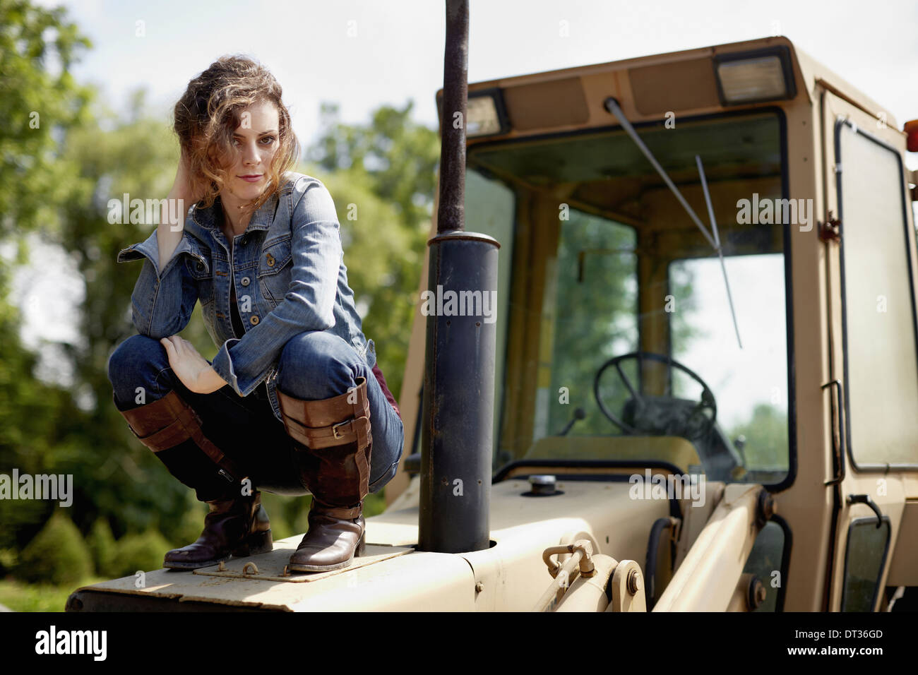 A young woman in denim jacket and boots on the hood of a tractor - Stock Image