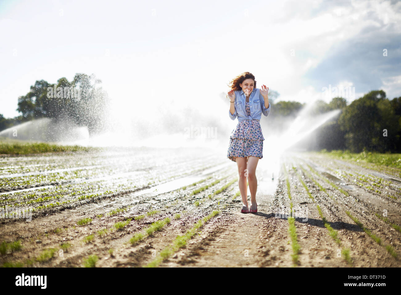 A young woman in denim jacket standing in a field irrigation sprinklers working in the background - Stock Image