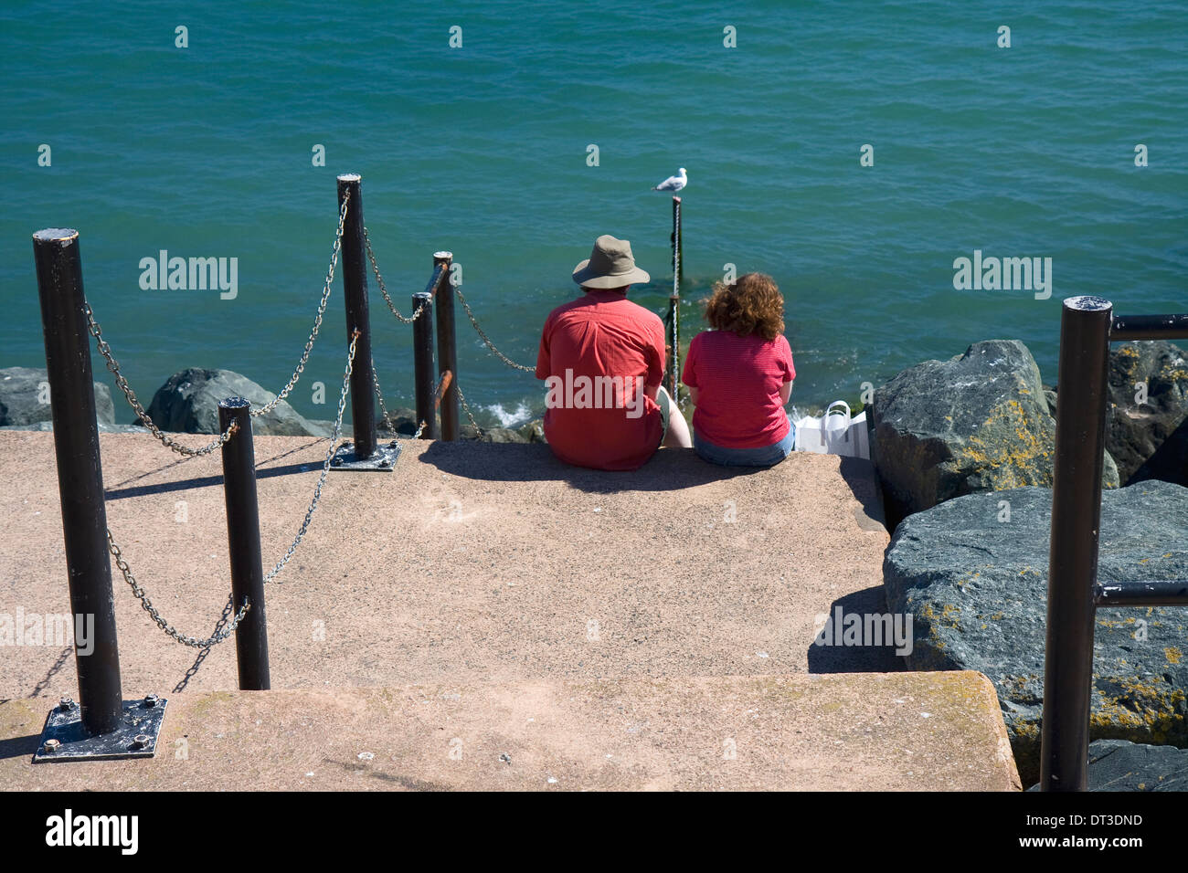 couple-in-red-shirts-sitting-beside-the-sea-at-lyme-regis-dorset-DT3DND.jpg