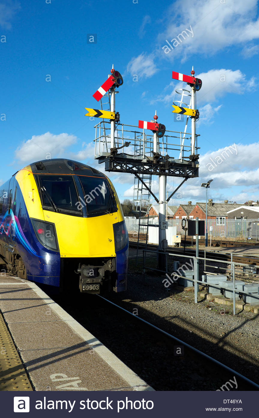 A train at Worcester Shrub Hill railway station, passing the old semaphore signals. Worcester, UK, February 2014. Stock Photo