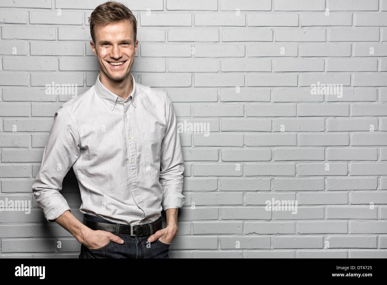 Male casual portrait smiling studio brick looking camera - Stock Image