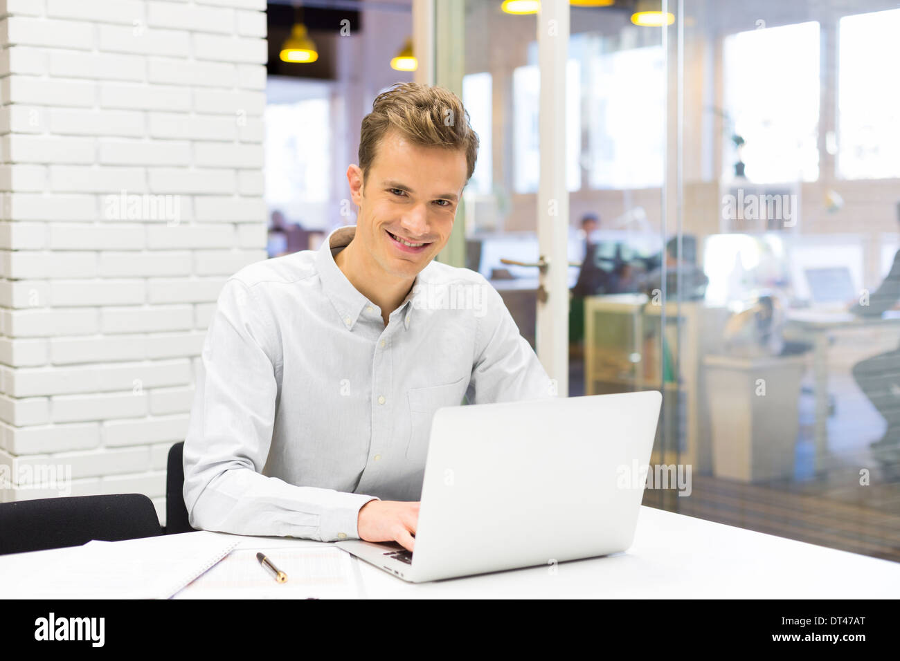 Male business computer desk looking camera - Stock Image