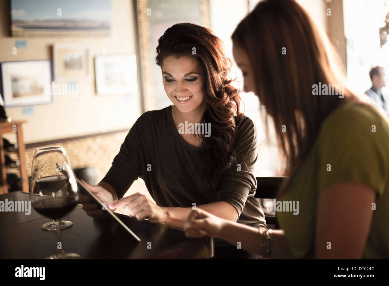 Businesswomen looking at digital tablet in a wine bar - Stock Image