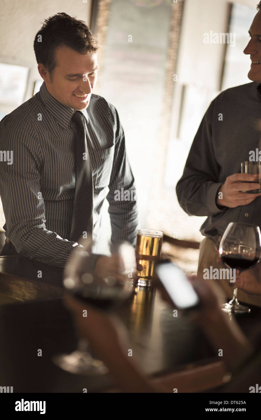 Business friends enjoying drinks in a wine bar - Stock Image