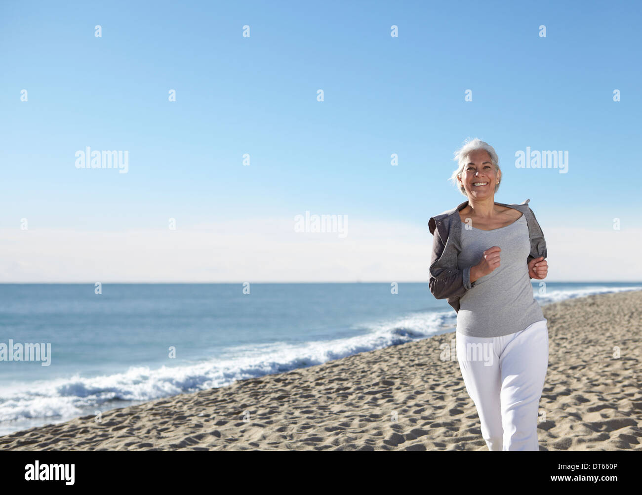 Mature woman jogging on beach - Stock Image