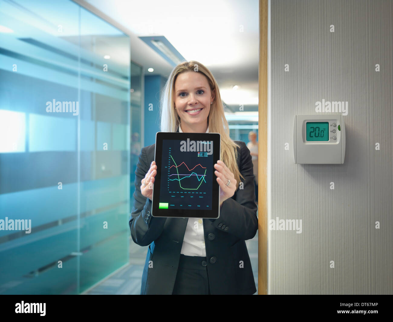 Portrait of office worker holding digital tablet next to office thermostat adjusted to make energy savings - Stock Image