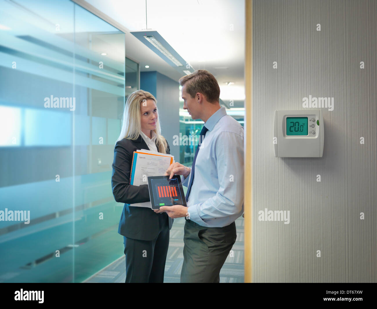Office workers holding digital tablet and files discussing office energy use - Stock Image