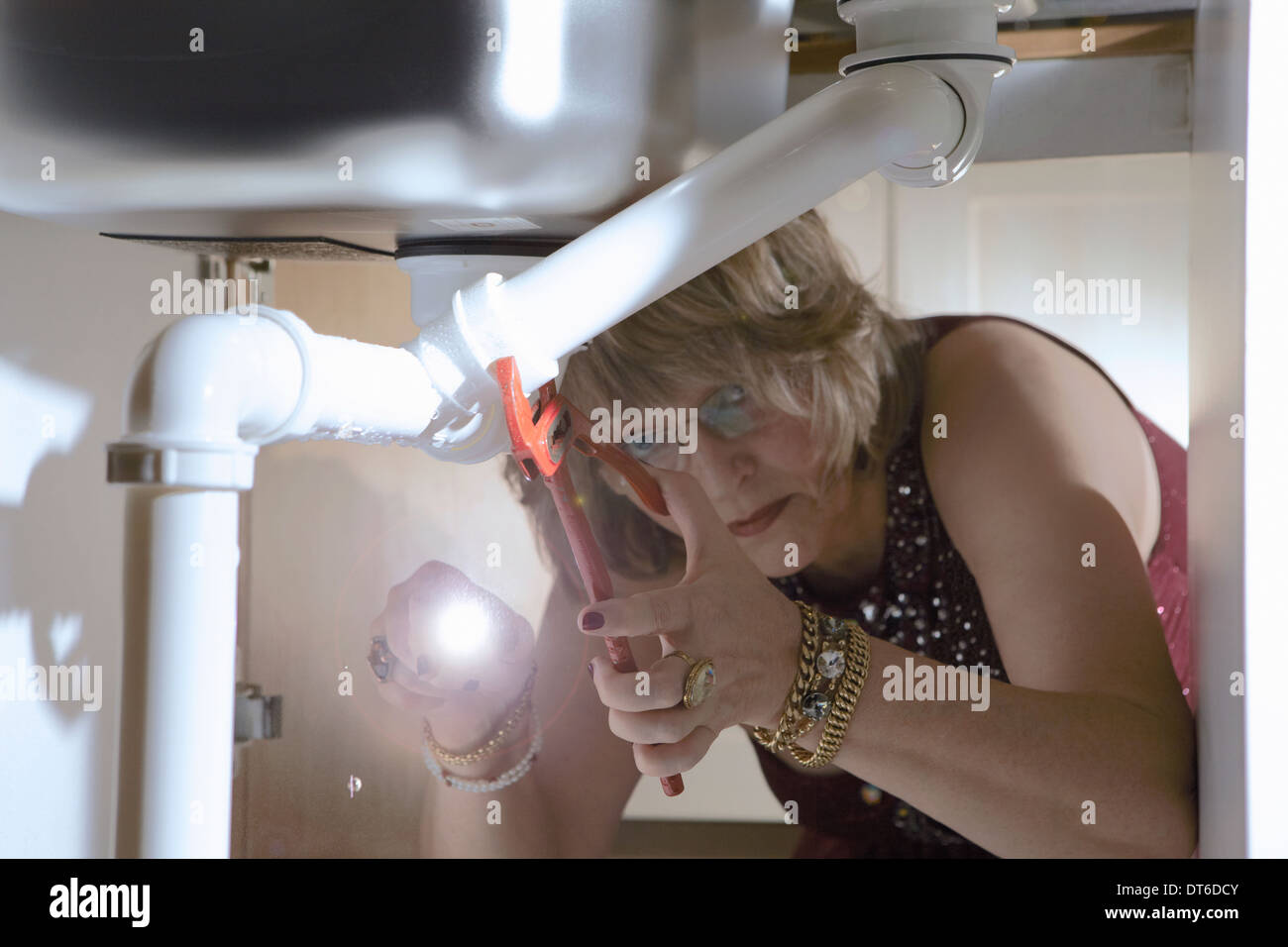 Senior woman in evening wear fixing pipes under kitchen sink - Stock Image