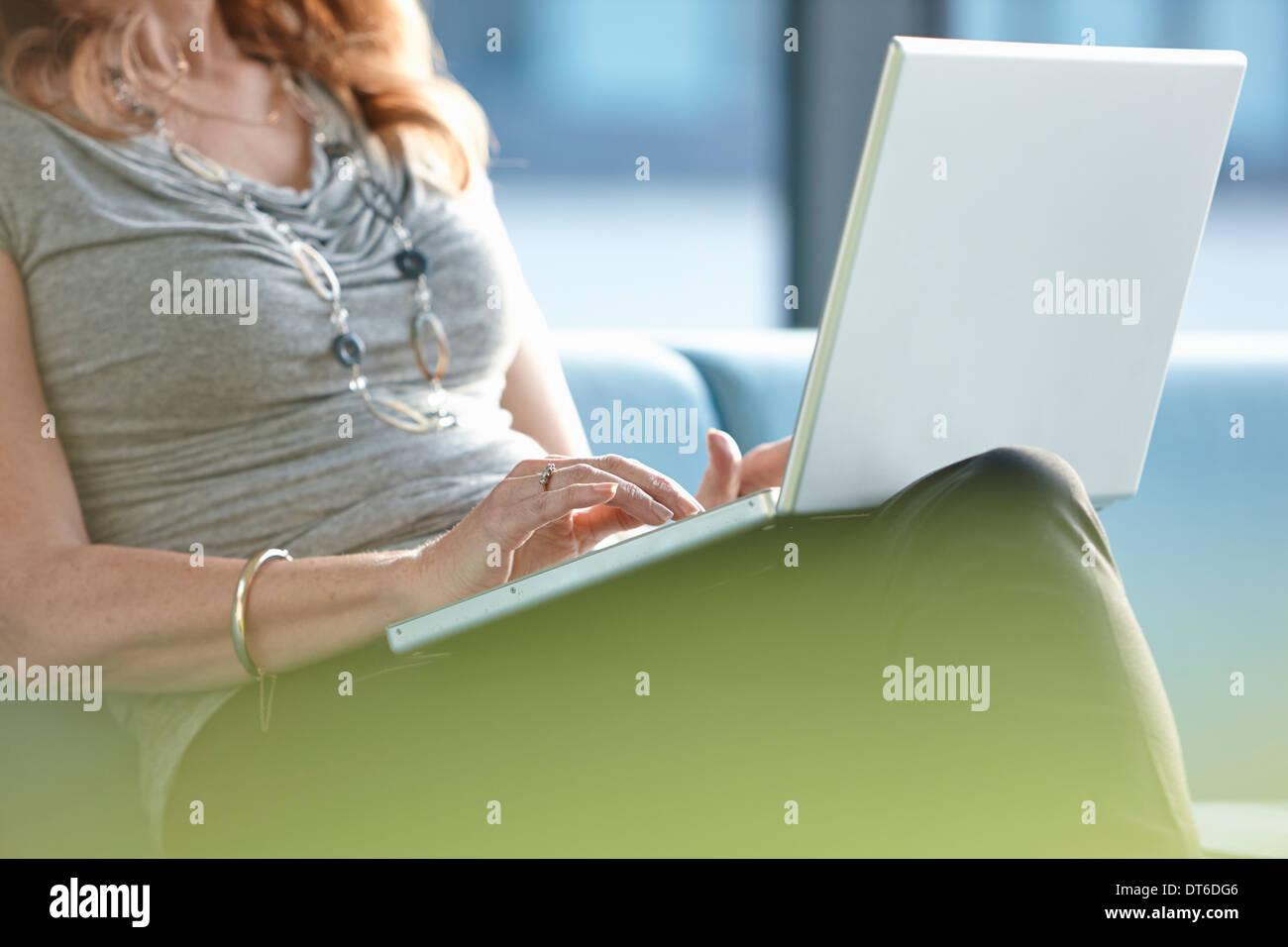 Businesswoman using laptop - Stock Image