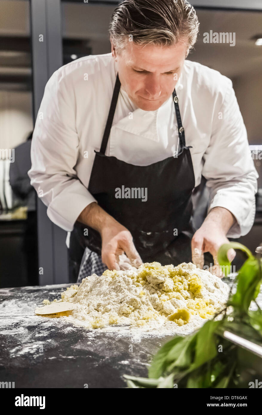 Chef mixing gnocchi dough in commercial kitchen - Stock Image