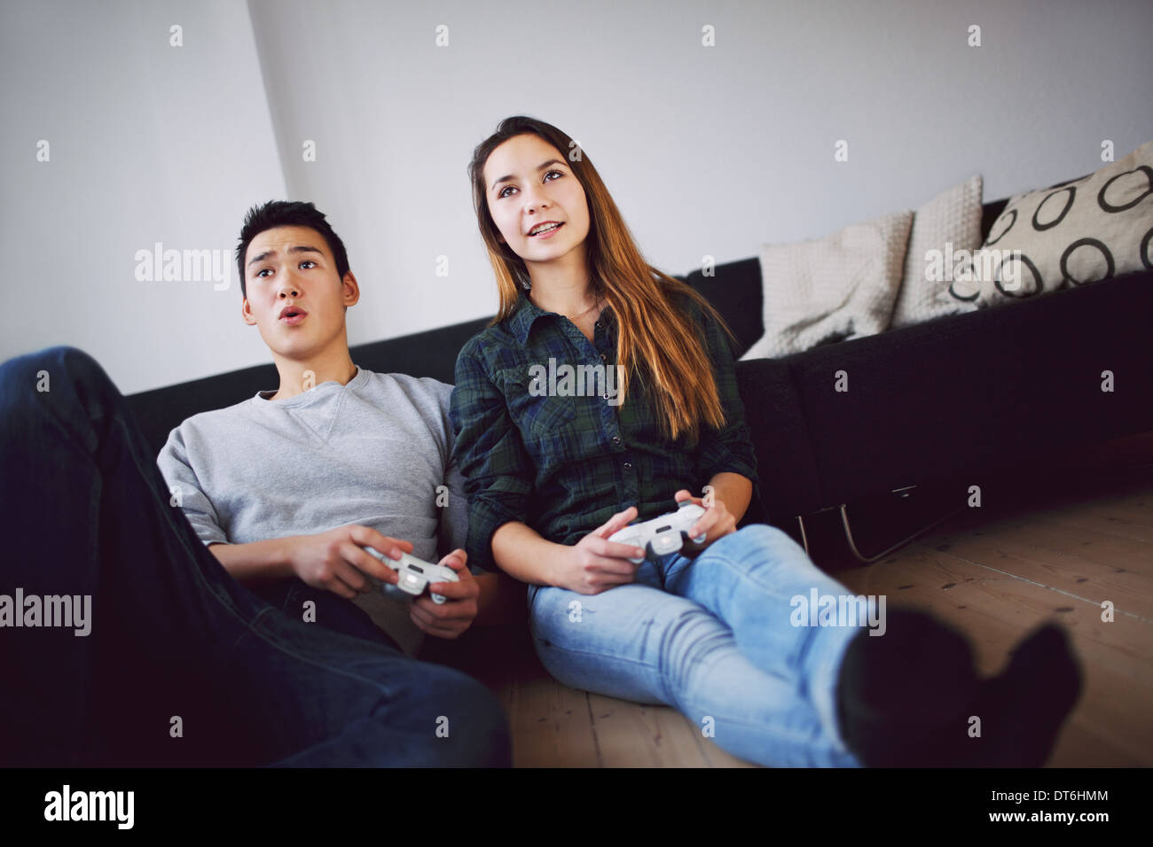 Young couple playing video games together while sitting in their living room. Mixed race teenage couple holding - Stock Image