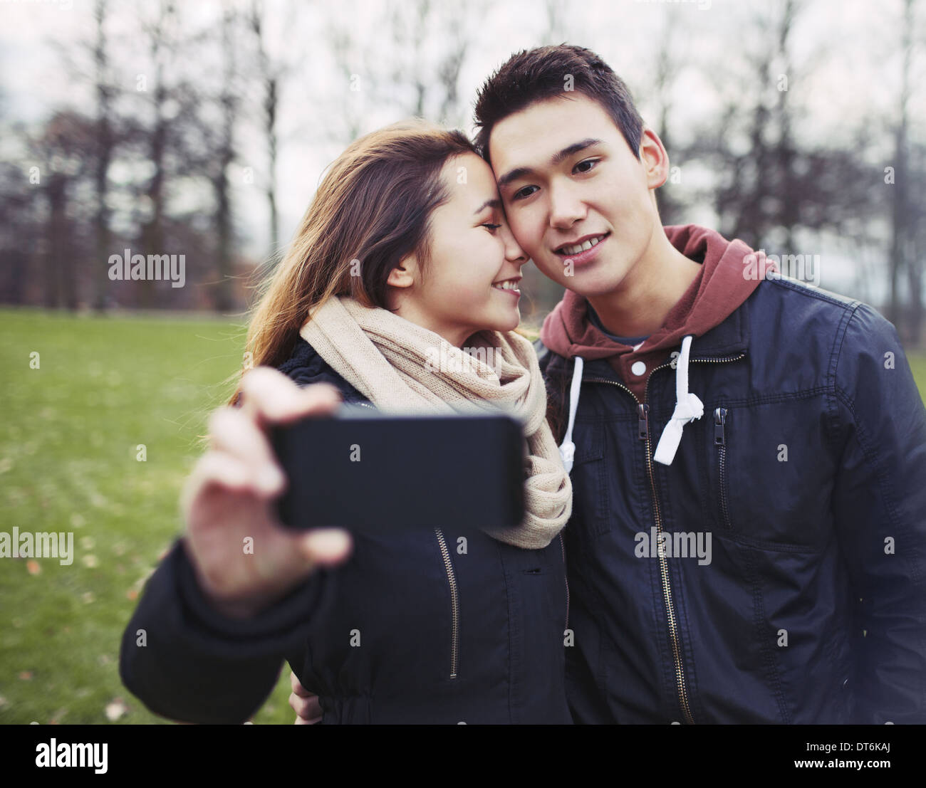 Affectionate young couple taking pictures using a smart phone at the park. Teenage boy and girl in love photographing - Stock Image