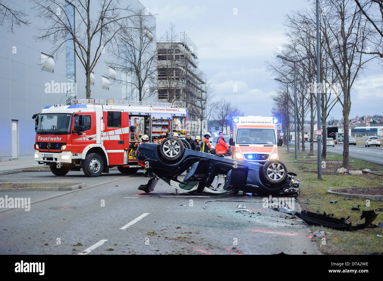 Ambulance and a fire engine at the scene of an accident, BMW sports car on its roof, overturned car, Germany - Stock Image