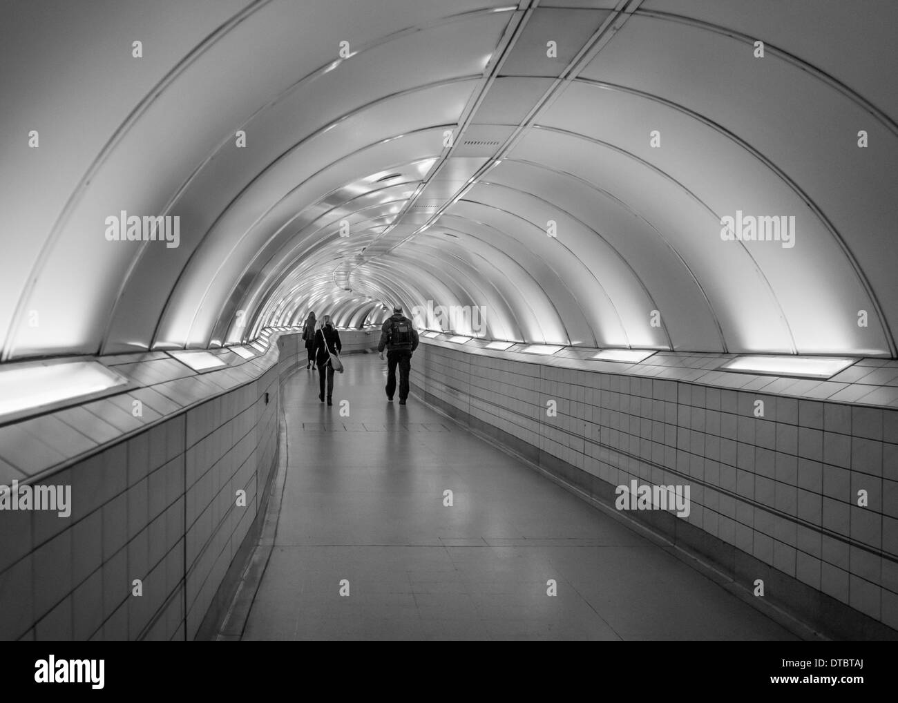 Commuters walk in long underground tunnel of London Tube system ...