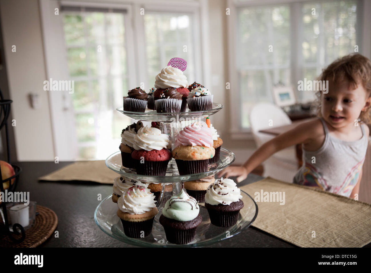 Female toddler looking at cake stand full of cupcakes - Stock Image