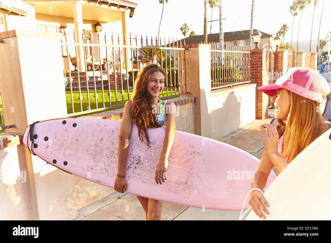 Two girls carrying surfboards laughing and smiling - Stock Image